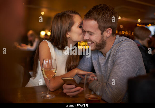 Romantic Couple Sitting And Talking In Wine Bar Together - Stock-Bilder