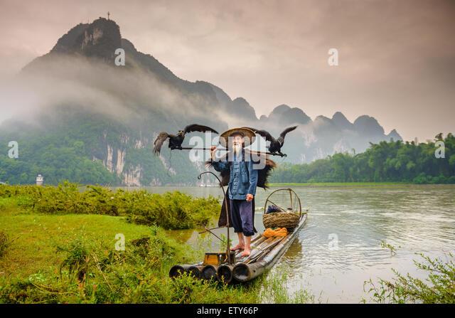 Cormorant fisherman and his birds on the Li River in Yangshuo, Guangxi, China. - Stock Image