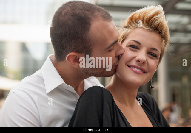 Smiling couple kissing outdoors - Stock Image