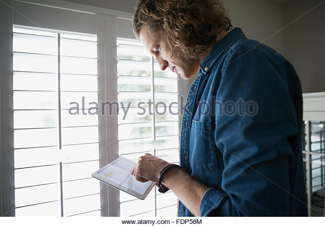 Man using digital tablet at window - Stock Image