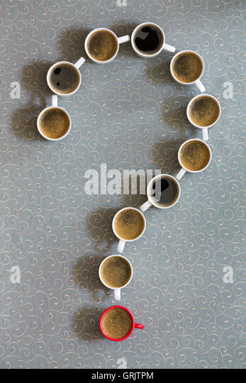 White coffee mugs filled with milky freshly brewed coffee arranged as a question mark with a single red cup as the - Stock Image