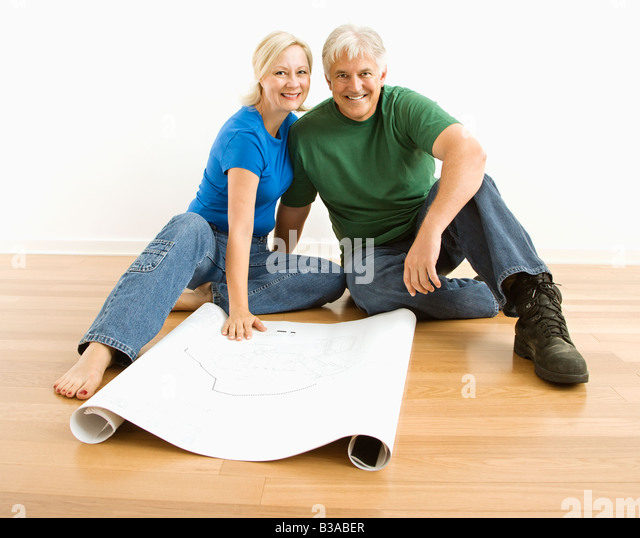 Middle aged couple sitting on floor with architectural blueprints - Stock-Bilder