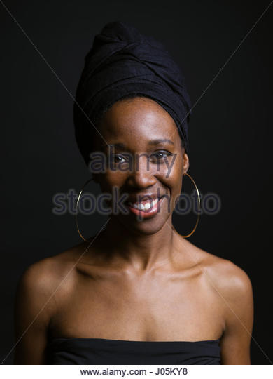 Portrait smiling African American woman wearing headscarf against black background - Stock Image