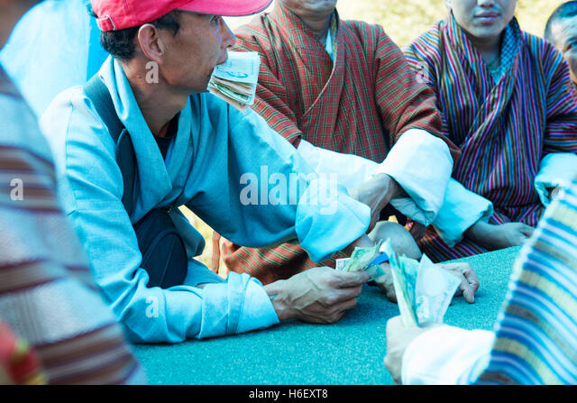 Gambler holding cash notes in his mouth while gambling during the Menji harvest festival. - Stock Image