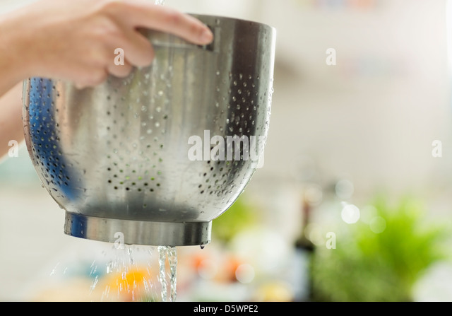 Woman straining food in kitchen - Stock-Bilder