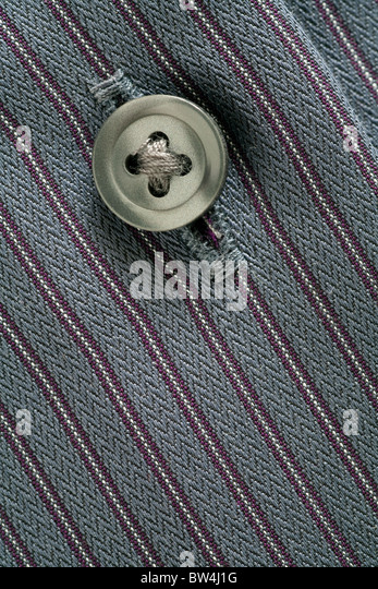 Close up image of the button and button hole on a man's striped shirt - Stock Image