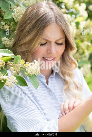 MODEL RELEASED. Young woman scratching arm. - Stock-Bilder