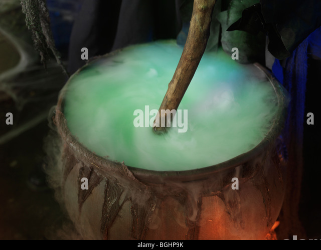 Witch stirring a steaming potion in a cauldron inside a witch cabin - Stock Image