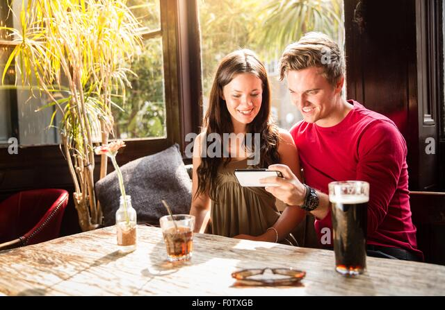 Couple enjoying drinks looking at smartphone together - Stock Image