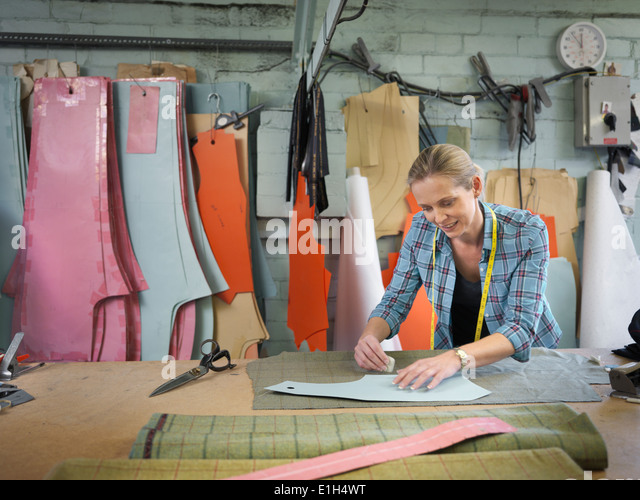 Fashion designer marking up cloth in clothing factory - Stock Image