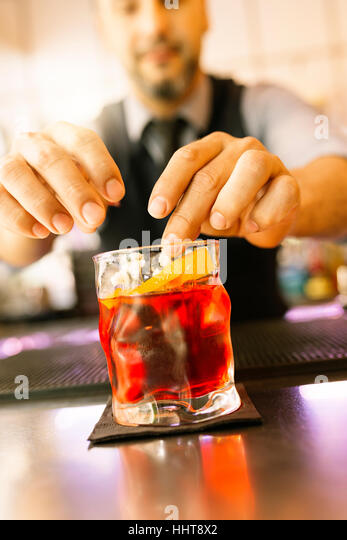 Expert barman is making cocktail at night club. - Stock Image