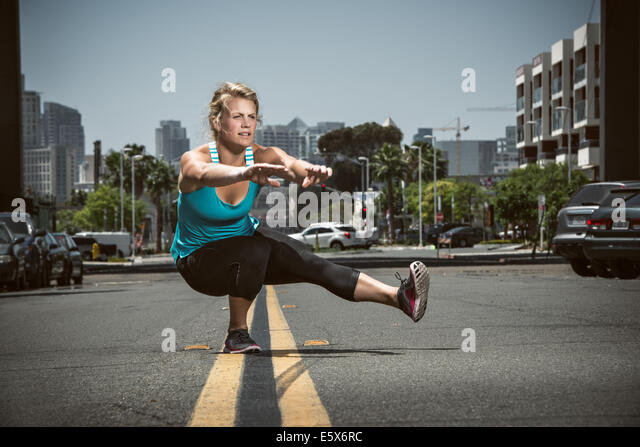 Young adult woman balancing on one foot in road - Stock Image