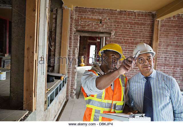 Tradesman and architect discussing work order at construction site - Stock Image