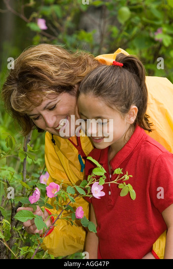 Mother Daughter Enjoy Flowers Botanical Garden AK Anchorage Father Looking On SC Summer - Stock Image