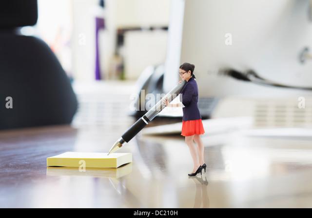 Businesswoman writing on large adhesive label on oversized desk - Stock Image