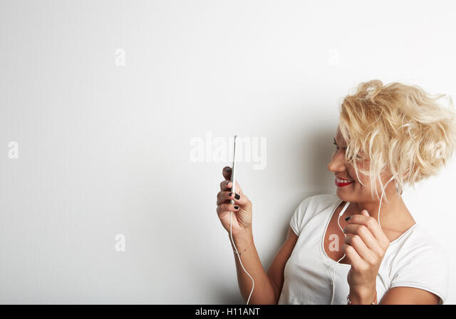 Stylish Female Making Selfie or Cheking Email via Smartphone While Standing Against White Background and Listening - Stock Image
