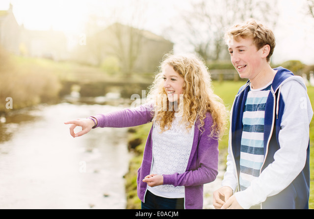 Teenage brother and sister on rural riverbank - Stock Image