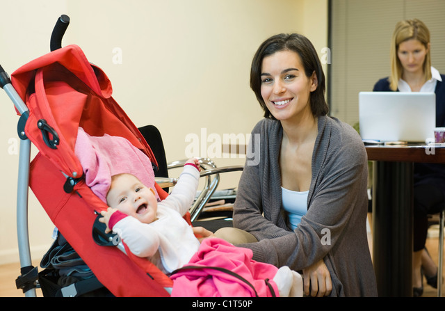 Mother posing with baby in office - Stock Image
