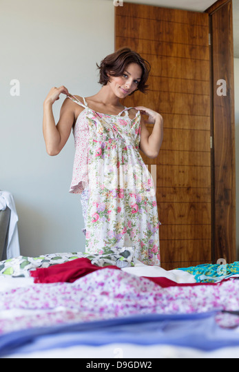 Woman trying on a dress at home - Stock Image