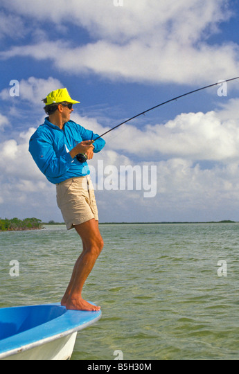 bonefishing angler fly rod bent standing boat bow - Stock Image