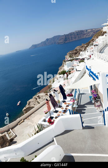 Traditional homes and hotels in the busy town of Oia, on the Greek Island of Santorini. The narrow paths wind through - Stock Image