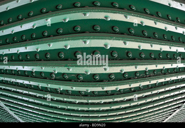 Rivets in steel girders on underside of railway bridge close up as pattern abstract background image manipulated - Stock Image