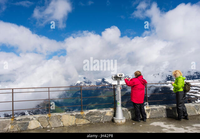 Tourists looking at scenic view from viewing platform on Dalsnibba mountain overlooking Geirangerfjorden. Geiranger - Stock Image
