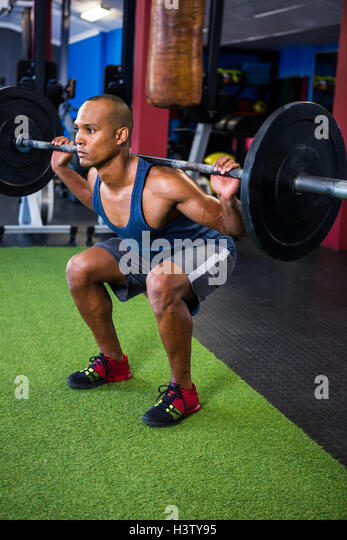 Young man weightlifting in gym - Stock Image