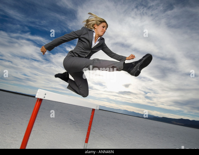 Businesswoman jumping over hurdle, Salt Flats, Utah, United States - Stock Image