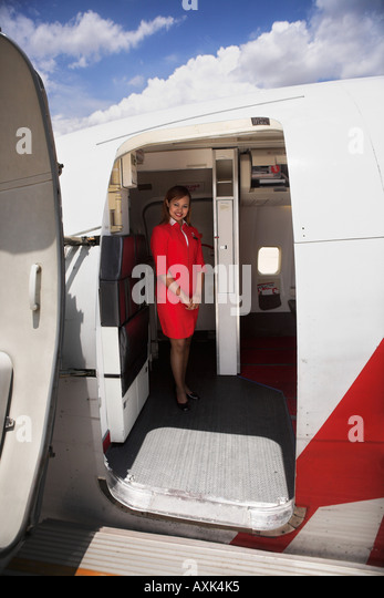 lady in red on plane fly sky clouds open enter welcome door entry fly trip travel vacation transportation blue white - Stock Image