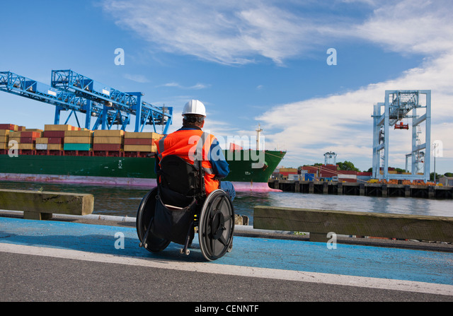 Transportation engineer in wheelchair inspecting container ship at shipping port - Stock Image