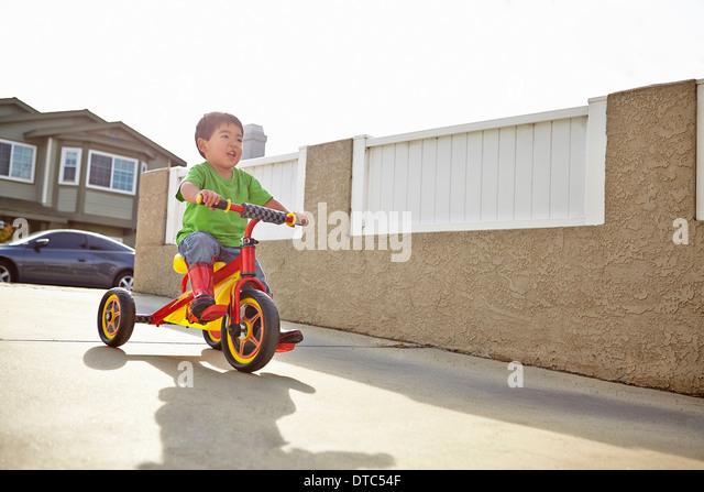 Boy cycling on driveway - Stock Image