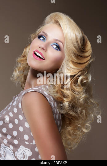 Happy Woman with Frizzy Blond Hairs Looking Up - Stock Image