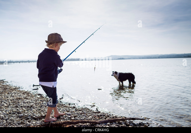 Boy fishing with dog in creek - Stock Image