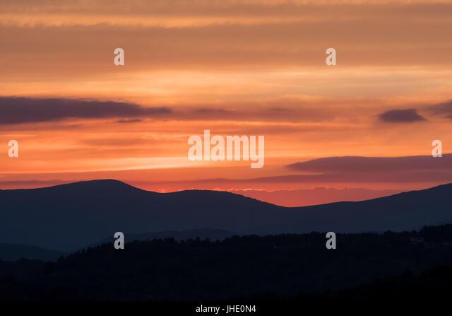 Bright Orange Cloudy Sky Above Blue Ridge Mountain Ridges - Stock Image