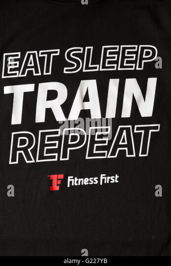 eat sleep train repeat - details on Fitness First black t-shirt - Stock Image