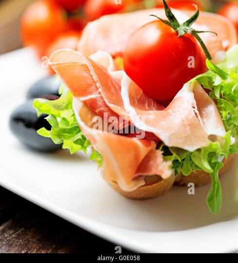 thin slices of prosciutto with olives and tomato on plate - Stock Image