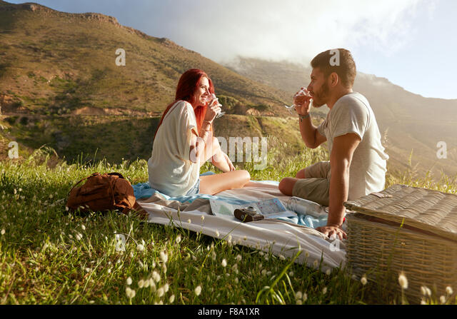 Outdoor shot of a young couple drinking wine. Relaxed man and woman on summer vacation in countryside. - Stock-Bilder