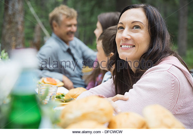 Woman enjoying meal with family at campsite - Stock-Bilder