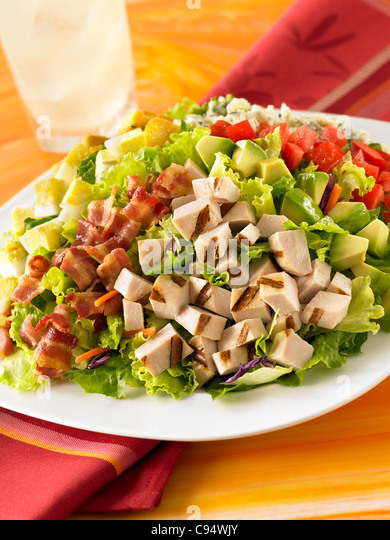 A Cobb salad with diced chicken, bacon, avocado, tomatoes, cheese and egg - Stock Image