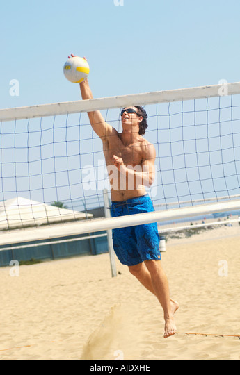 Young man jumping, hitting volleyball over net on beach - Stock Image