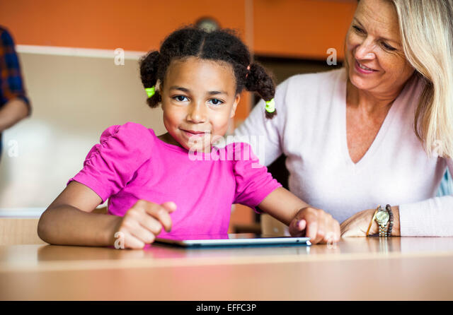 Happy teacher with girl using tablet computer at desk - Stock Image