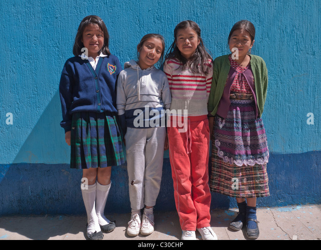 Four primary school students stand against a bright blue colored wall of their school in Totonicapan, Guatemala - Stock Image