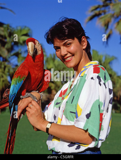 Woman holding Green-winged Macaw at Loro Parque, Puerto de La Cruz, Tenerife, Canary Islands, Spain - Stock Image