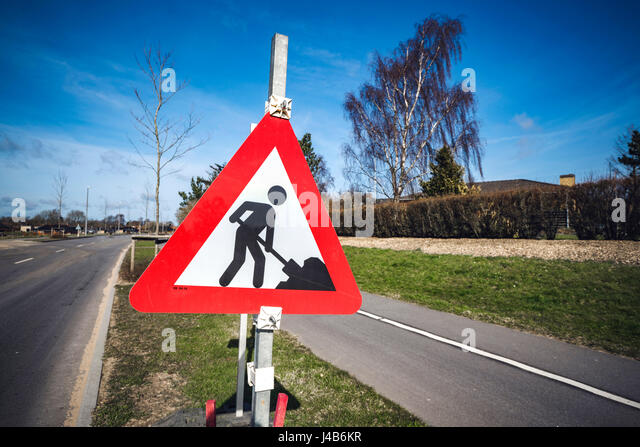 Road construction sign by a roadside in a city on a sunny day with blue sky - Stock Image
