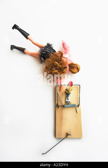 Barbie caught in a mousetrap reaching for lipstick bait - Stock-Bilder