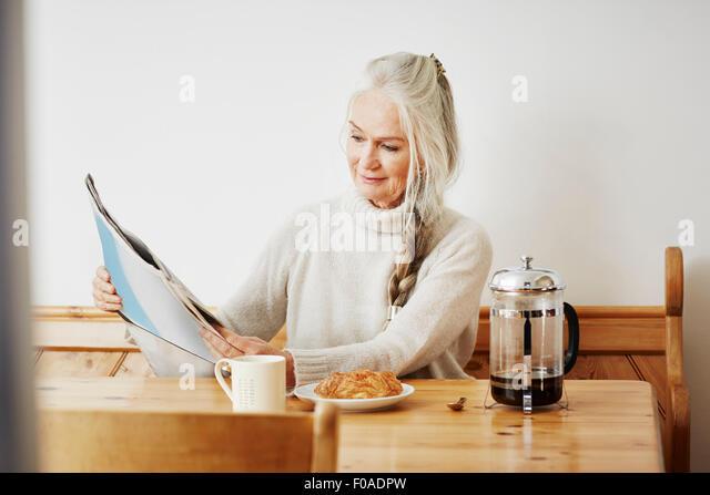 Senior woman reading newspaper at breakfast - Stock Image