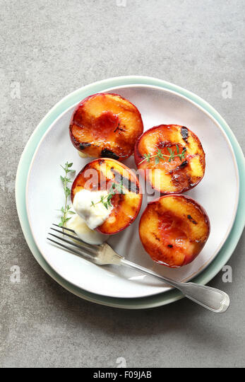 Plate with grilled peach with greek yogurt,honey and decorated with fresh thyme - Stock Image