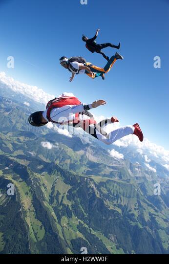 Three skydivers tracking above Gruyeres in Switzerland - Stock Image