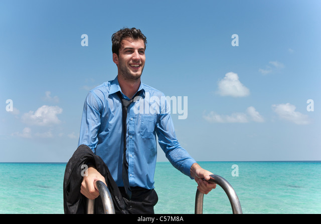 Businessman in wet clothes climbing dock - Stock Image